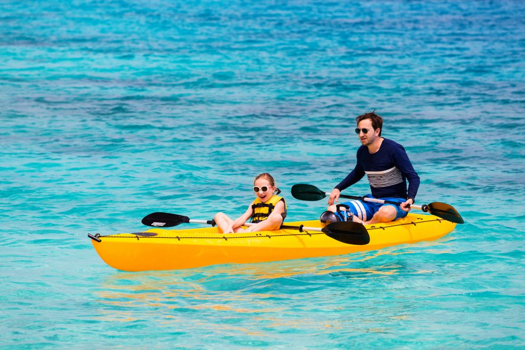Family of father and daughter paddling on  kayaks b< Tripps Travel Network